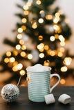 Taza de café de la Navidad con las melcochas en el fondo de las luces y de las decoraciones del ` s del Año Nuevo Fotografía de archivo
