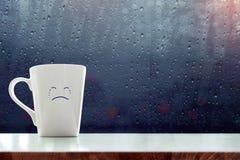 Taza de café de la tristeza con la historieta gritadora de la cara dentro del cuarto, azul Fotos de archivo