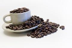 Taza de café llenada de las habas, desbordando Imagen de archivo