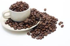 Taza de café llenada de las habas, desbordando Foto de archivo libre de regalías
