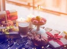 Taza de café o de té cerca de una calabaza, de los regalos y de las velas Imagen de archivo