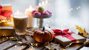 Taza de café o de té cerca de una calabaza, de los regalos y de las velas Fotografía de archivo libre de regalías