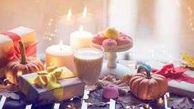 Taza de café o de té cerca de una calabaza, de los regalos y de las velas Foto de archivo