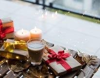 Taza de café o de té cerca de una calabaza, de los regalos y de las velas Foto de archivo libre de regalías