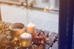 Taza de café o de té cerca de una calabaza y de velas Fotos de archivo libres de regalías