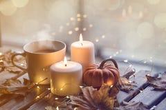 Taza de café o de té cerca de una calabaza y de velas Imágenes de archivo libres de regalías