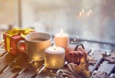 Taza de café o de té cerca de una calabaza y de velas Imagenes de archivo