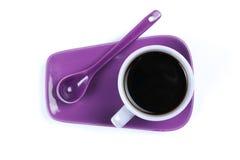 Taza de café púrpura con el platillo y la cuchara aislados en el fondo blanco Foto de archivo