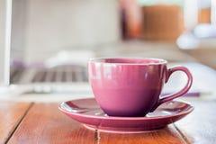 Taza de café púrpura en la estación de trabajo Fotos de archivo