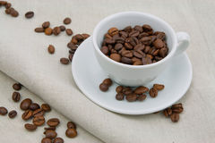 Taza de café por completo de granos de café Imagen de archivo libre de regalías
