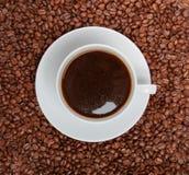 Taza de café que se sienta en una cama de los granos de café fotos de archivo