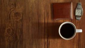 Taza de café, reloj, opinión superior de la cartera sobre fondo de madera de la tabla Imágenes de archivo libres de regalías