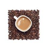 Taza de café rodeada por los granos de café fotos de archivo