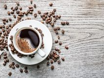 Taza de café rodeada por los granos de café Visión superior imagen de archivo libre de regalías