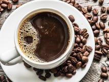 Taza de café rodeada por los granos de café Visión superior fotos de archivo libres de regalías