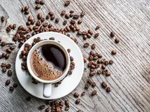 Taza de café rodeada por los granos de café Visión superior fotos de archivo