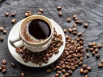 Taza de café rodeada por los granos de café Visión superior fotografía de archivo