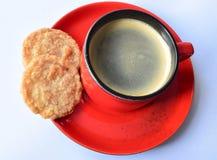 Taza de café roja con dos galletas Foto de archivo libre de regalías
