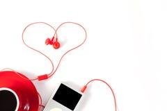 Taza de café roja con el jugador de música y el auricular rojo en el backg blanco Imagenes de archivo