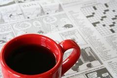 Taza de café roja con el periódico en fondo Fotografía de archivo libre de regalías