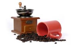 Taza de café roja con una amoladora de café Fotografía de archivo
