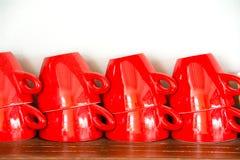 Taza de café roja en el estante de madera Imagenes de archivo