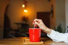 Taza de café roja en un café en la tabla Lugar para el resto Imagen de archivo libre de regalías