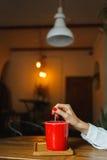 Taza de café roja en un café en la tabla Lugar para el resto Fotografía de archivo libre de regalías