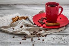 Taza de café roja en una placa, fondo de madera, bebida, mañana de la Navidad Imágenes de archivo libres de regalías