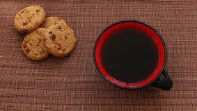 Taza de café roja grande con las galletas de microprocesador de chocolate Foto de archivo