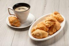 Taza de café sólo con el platillo, cruasanes frescos en el porce blanco Foto de archivo