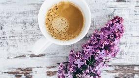 Taza de café sólo en la tabla de madera del vintage con la rama de la opinión superior de la lila Fotografía de archivo libre de regalías