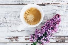 Taza de café sólo en la tabla de madera del vintage con la rama de la opinión superior de la lila Foto de archivo