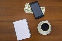 Taza de café, de smartphone, de dólares, de libreta y de pluma en el escritorio de madera Foto de archivo