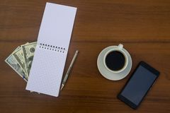 Taza de café, de smartphone, de dólares, de libreta y de pluma en el escritorio de madera Imagen de archivo libre de regalías