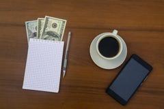 Taza de café, de smartphone, de dólares, de libreta y de pluma en el escritorio de madera Imagenes de archivo