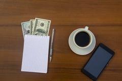 Taza de café, de smartphone, de dólares, de libreta y de pluma en el escritorio de madera Fotos de archivo libres de regalías