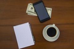 Taza de café, de smartphone, de dólares, de libreta y de pluma en el de madera Imagen de archivo