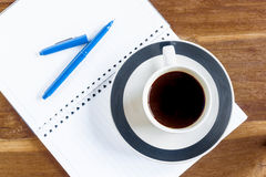 Taza de café sobre el cuaderno en la tabla de madera foto de archivo