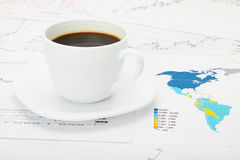 Taza de café sobre mapa del mundo y documentos financieros Fotografía de archivo libre de regalías