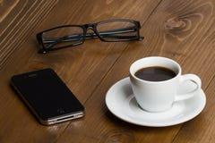 Taza de café, teléfono móvil a los vidrios en un de madera Fotos de archivo