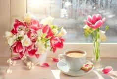 Taza de café, tulipanes rosados y fresia blanca - en el tablero de ventana, fotos de archivo