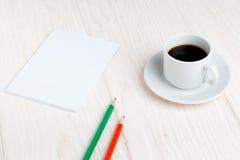 Taza de café, un cuaderno, lápices en la tabla Imágenes de archivo libres de regalías