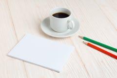 Taza de café, un cuaderno, lápices en la tabla Foto de archivo libre de regalías