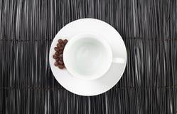 Taza de café vacía con los granos de café en fondo negro de la estera de la paja Foto de archivo libre de regalías