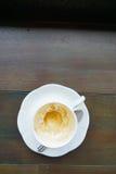 Taza de café vacía después de la bebida en la tabla de madera fotos de archivo