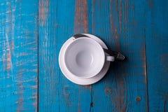 Taza de café vacía en fondo de madera azul foto de archivo