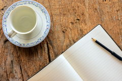 Taza de café vacía y páginas en blanco de la nota Foto de archivo libre de regalías