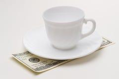 Taza de café vacía y 100 USD Foto de archivo