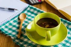 Taza de café verde con los materiales de oficina Imágenes de archivo libres de regalías